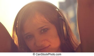 Slow motion of Young woman listening to music in headphones at city sunset . Dancing, flirting and sending kisses to the camera