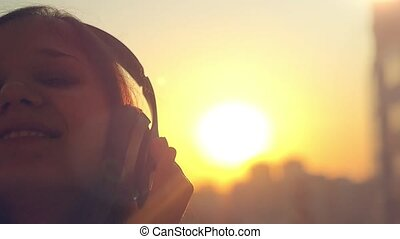 Slow motion of Young woman listening to music in headphones at city sunset . Flirting and sending kisses to the camera