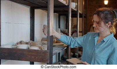 Slow motion of young woman looking at hand-made earthware ...