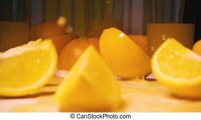 Slow motion orange falls on the table