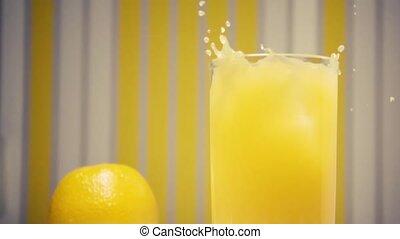 Slow motion orange juice with ice cubes