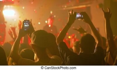 Slow motion: people hands silhouette taking photo or recording video of live music concert with smartphone. Bright colorful stage lighting. Nightlife, technology, photography, entertainment concept