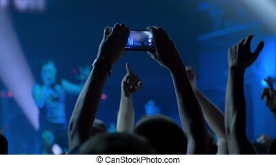 Slow motion: people hands silhouette taking photo or recording video of live music concert with smartphone. Crowd partying in front of stage. Photography, entertainment, technology concept