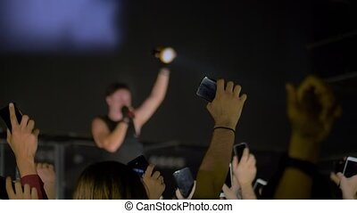 Slow motion: people crowd partying, cheering, rising hands up and holding smartphones with flashlights at rock concert in front of stage of nightclub. Nightlife and entertainment concept