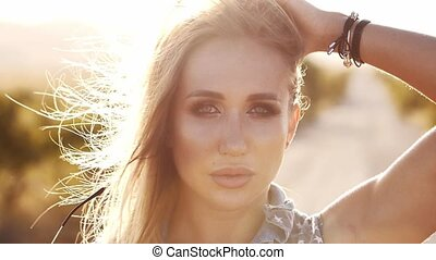 slow motion portrait of a young woman with fluttering in the wind in the sun's hair