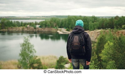Slow motion portrait of active young man traveller with knapsack walking down the mountain and watching great view of lakes and forests and cloudy sky.