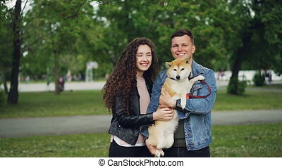 Slow motion portrait of adorable couple and purebred dog...