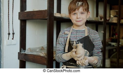 Slow motion portrait of adorable kid with dirty face holding hand-made vase standing in pottery workshop alone looking at camera and smiling.