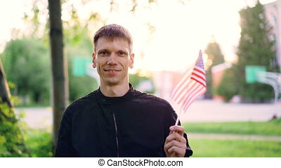 Slow motion portrait of American man waving national flag of...