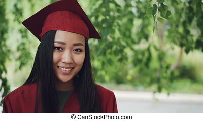 Slow motion portrait of attractive Asian girl graduating...