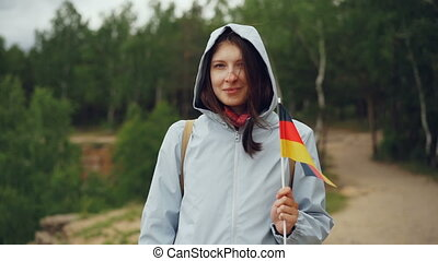 Slow motion portrait of attractive German woman holding flag of Germany, smiling and looking at camera. Patriotism, proud citizen and people concept.