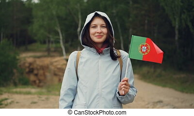 Slow motion portrait of attractive Portuguese girl holding...