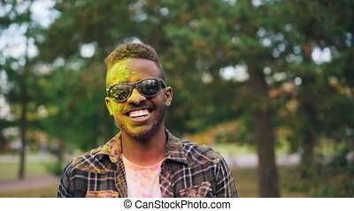 Slow motion portrait of bearded African American guy in sunglasses, face and hair covered with powder paint at Holi festival. Man is looking at camera and smiling.