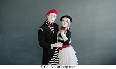 Slow motion portrait of beautiful couple of mimes girl and guy hugging then looking at camera sending air kisses. Love and relationship concept.