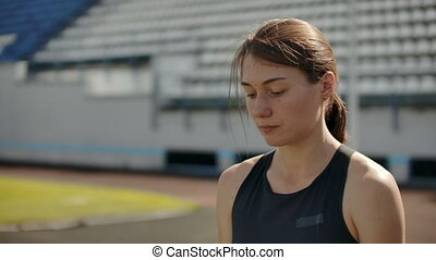 Slow motion portrait of beautiful woman running on the stadium bleachers with concentrated deep breathing and motivating myself and consciousness for the race. Discard unnecessary emotions and tune in to win, preparing for the race