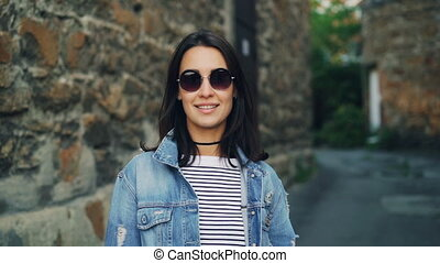 Slow motion portrait of beautiful young woman in sunglasses...