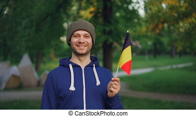 Slow motion portrait of Belgian man in sports jacket and hat...