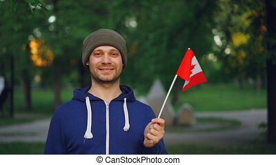 Slow motion portrait of Canadian sports fan waving official flag of Canada with happy smile and looking at camera. Beautiful landscape with trees and grass is in background.