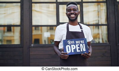 Slow motion portrait of cheerful African American businessman cafe owner holding we are open sign standing outside and looking at camera. Small business and successful youth concept.