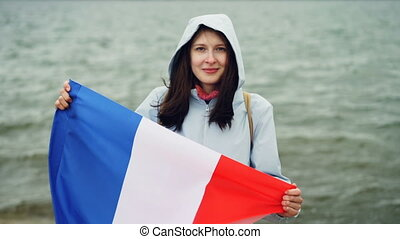 Slow motion portrait of cheerful French patriot holding...