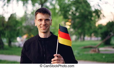 Slow motion portrait of cheerful German fan waving official flag and looking at camera while standing in great modern park with beautiful trees and lawns.