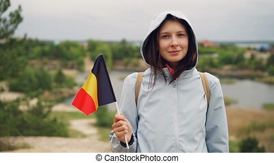 Slow motion portrait of cheerful tourist holding Belgian official flag and looking at camera with nice smile. Beautiful landscape with trees and lake is in background.