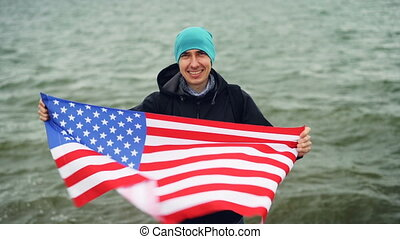 Slow motion portrait of cheerful traveller holding American...