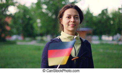 Slow motion portrait of cheerful young woman waving official German flag and looking at camera while standing in nice green park with beautiful trees and lawns.
