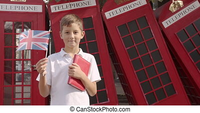 Slow motion portrait of cute boy waving British flag standing outdoors alone smiling looking at camera. On the background English red telephone booths. Travelling concept.