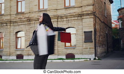 Slow motion portrait of excited young woman spinning in the street holding paper gift bags and looking at camera with happy smile. Shopping and positive emotions concept.