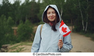 Slow motion portrait of female traveller pretty girl holding Canadian flag, smiling and looking at camera with beautiful natural landscape in background.