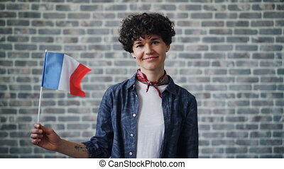 Slow motion portrait of French lady holding official flag of...