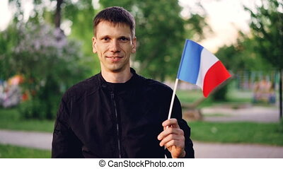 Slow motion portrait of Frenchman waving national flag...