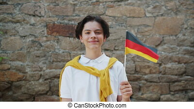 Slow motion portrait of German young boy waving flag of Germany smiling