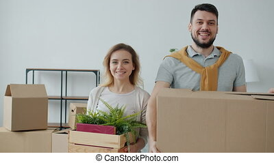 Slow motion portrait of girl and guy holding boxes smiling looking at camera in new apartment during relocation. Family life and real estate concept.