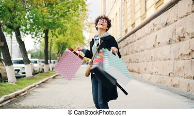 Slow motion portrait of glad curly-haired girl holding shopping bags and turning around with happy laughter enjoying purchases and free time. Shopaholism and city concept.