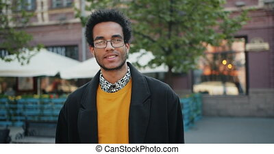 Slow motion portrait of good-looking African American man in glasses outdoors