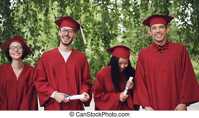 Slow motion portrait of graduating students standing in line holding diplomas and laughing looking at camera. Girls and guys are wearing mortar-boards and gowns.