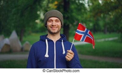 Slow motion portrait of handsome Norwegian sports fan waving...