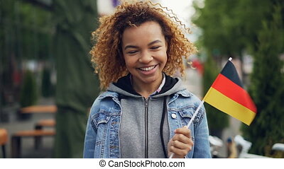 Slow motion portrait of happy African American woman smiling, holding German flag and looking at camera, bright flag is flutteting in the wind.