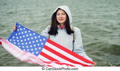 Slow motion portrait of happy American girl holding United ...