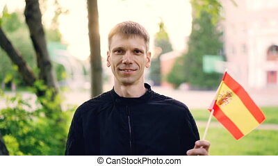Slow motion portrait of happy tourist young man waving Spanish flag and smiling standing in beautiful park with trees, green grass and nice buildings behind him.