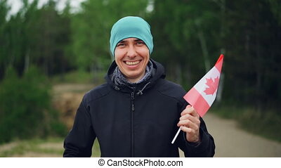 Slow motion portrait of happy world traveller holding Canadian flag, smiling and looking at camera with beautiful nature green wood in background.