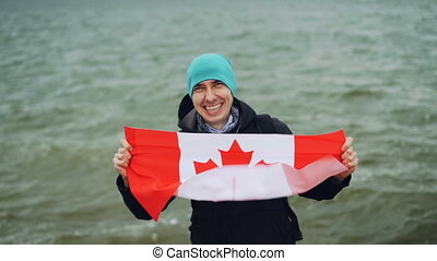Slow motion portrait of happy young man holding large textile flag of Canada, looking at camera and smiling with water waves in background. Tourism and nature concept.