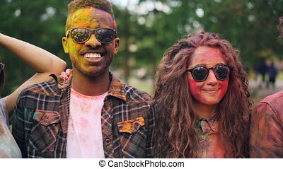 Slow motion portrait of happy young men and women with dirty faces and clothing looking at camera wearing sunglasses and smiling standing together in park.