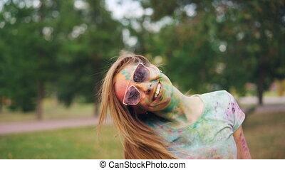 Slow motion portrait of joyful woman having fun at Holi...