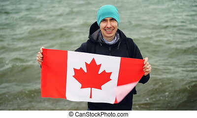 Slow motion portrait of joyful young man traveller holding Canadian flag in hands and looking at camera with glad smile. Sea waves are visible in background.