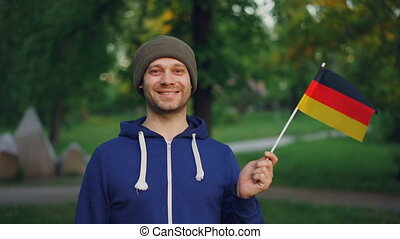 Slow motion portrait of male German sportsman handsome bearded man waving flag of Germany and smiling standing in city park. People, sports and patriotism concept.