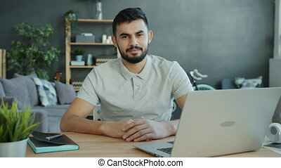 Slow motion portrait of good-looking Middle Eastern man at desk at home sitting alone and looking at camera wearing casual clothing. Freelancer and apartment concept.
