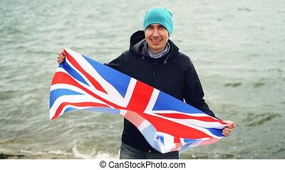 Slow motion portrait of patriotic Englishman holding flag of...